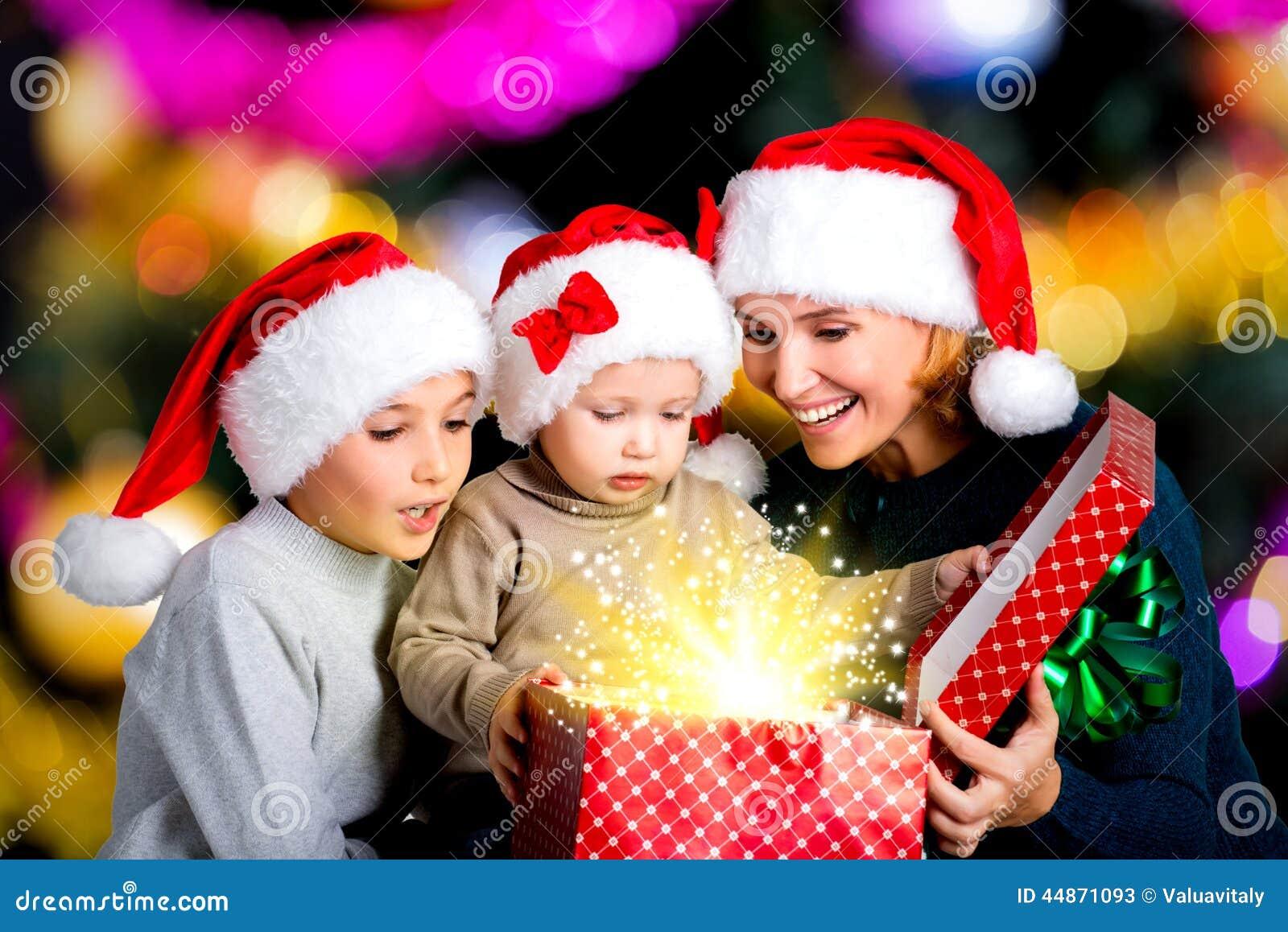 la m re avec des enfants ouvre la bo te avec des cadeaux de no l image stock image 44871093. Black Bedroom Furniture Sets. Home Design Ideas