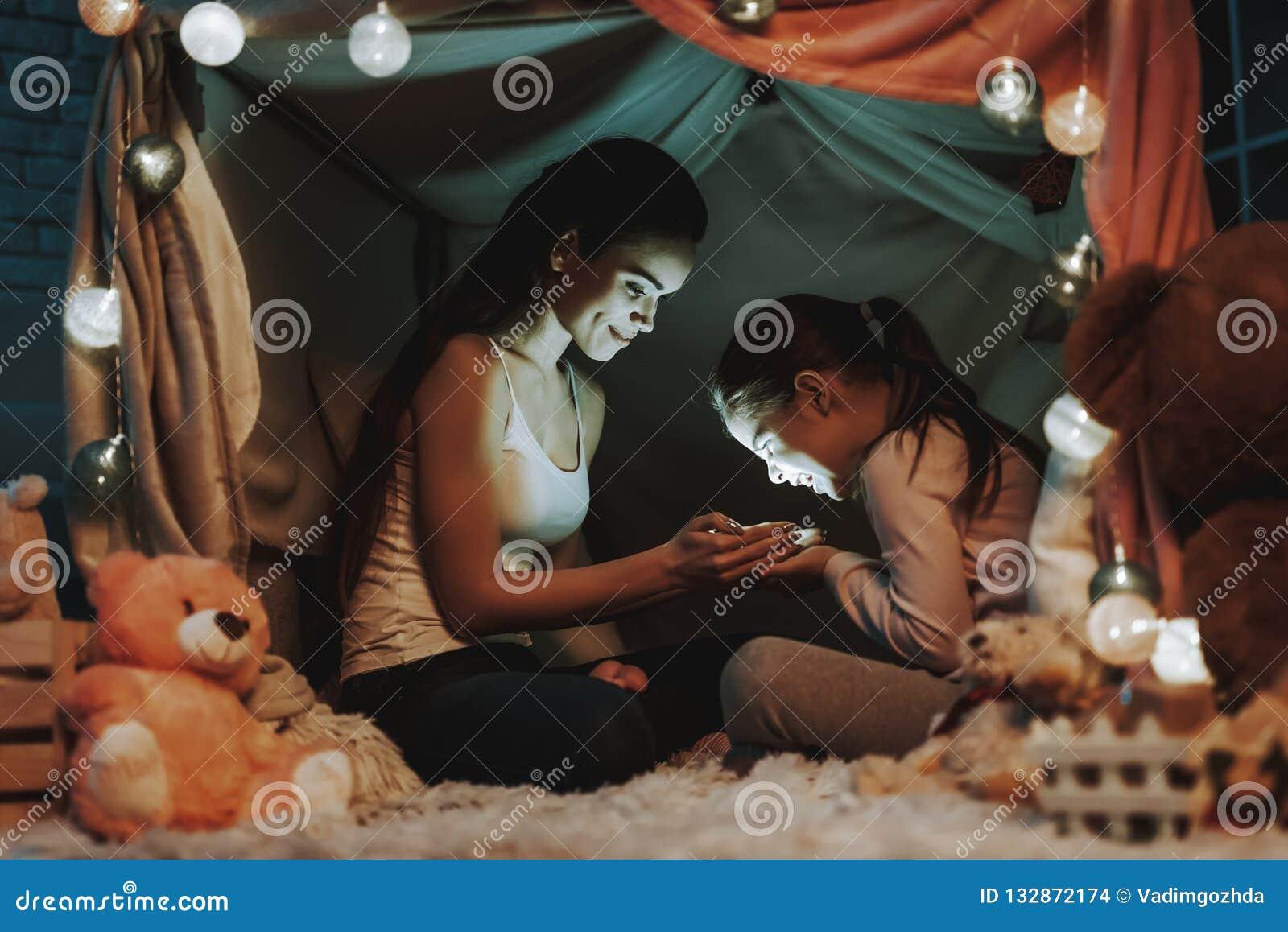 La mère et la fille tient une lumière dans des mains