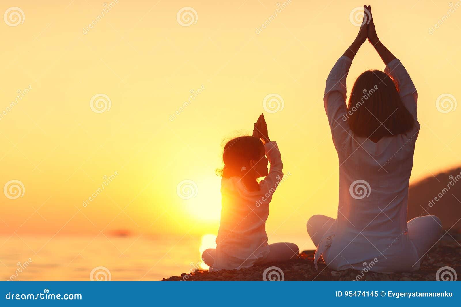 La mère heureuse et l enfant de famille faisant le yoga, méditent dans le posi de lotus