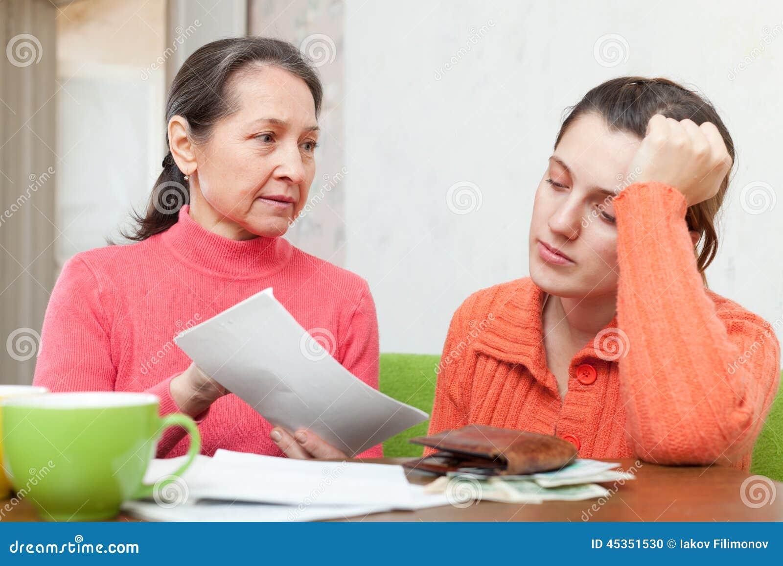 La mère mûre gronde la fille pour des factures ou des crédits