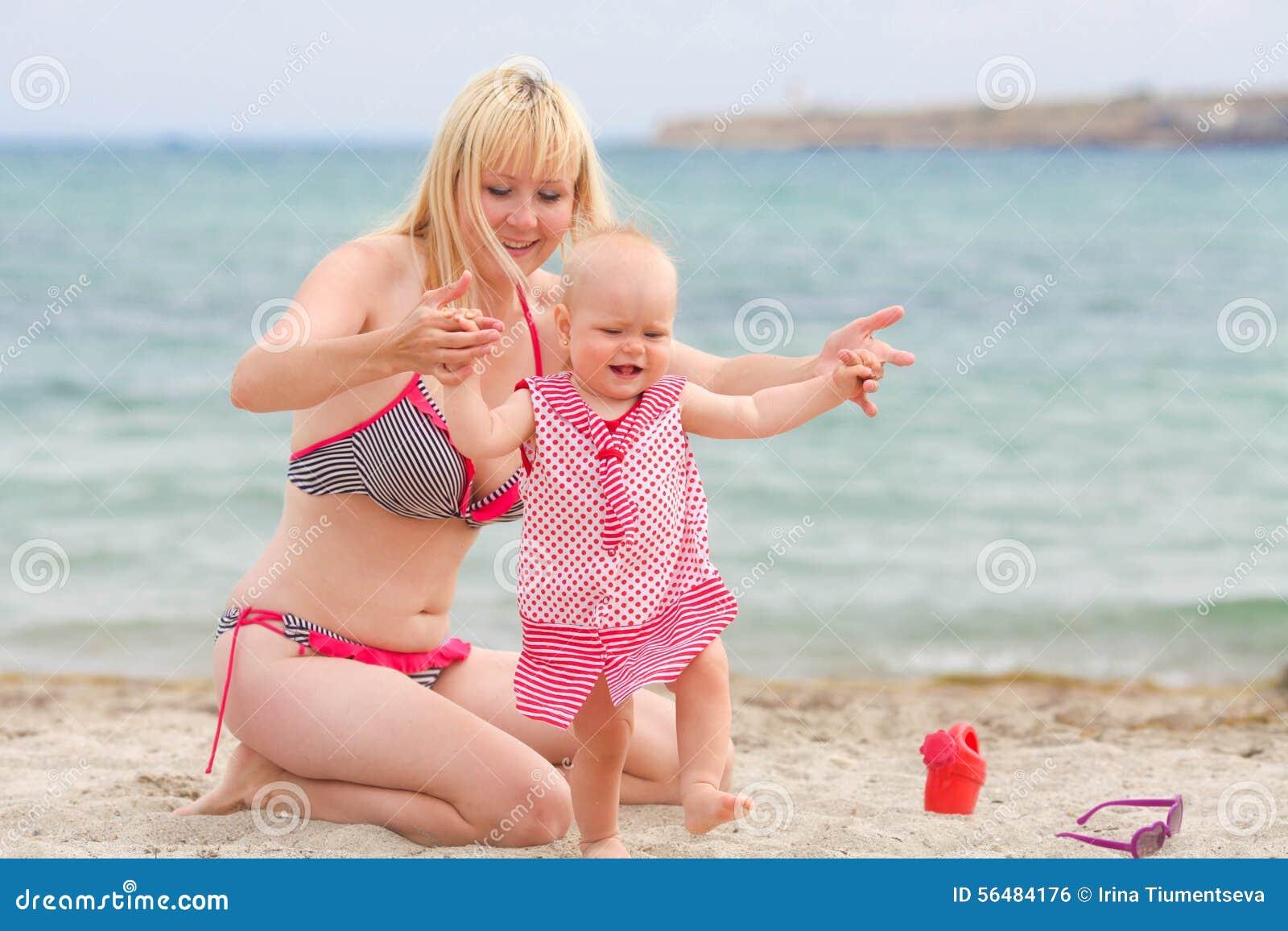 La mère marche sur la plage avec son petit daughte de bébé