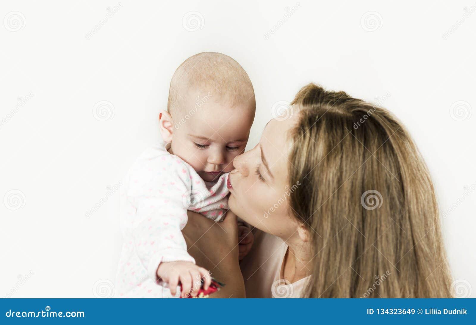 La mère tient le bébé dans des ses bras sur le fond d isolement