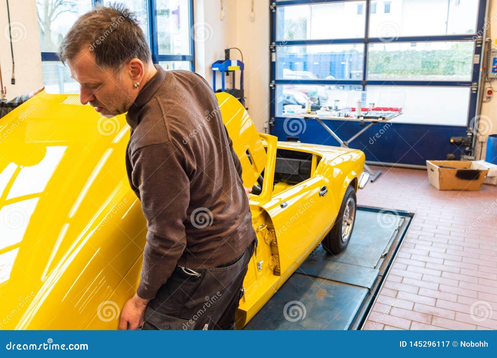 La mécanique de voiture aligne le capot correctement en se réunissant - atelier de réparation de Serie