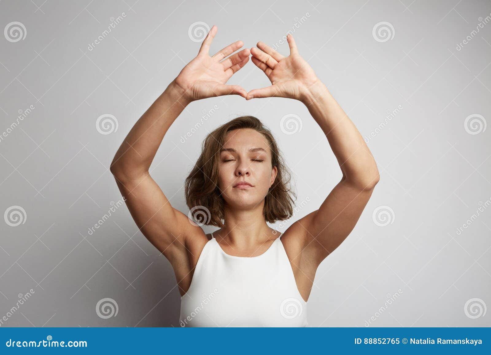 La méditation de pratique de jeune femme au bureau, yoga en ligne classe, prenant un temps de coupure pendant une minute