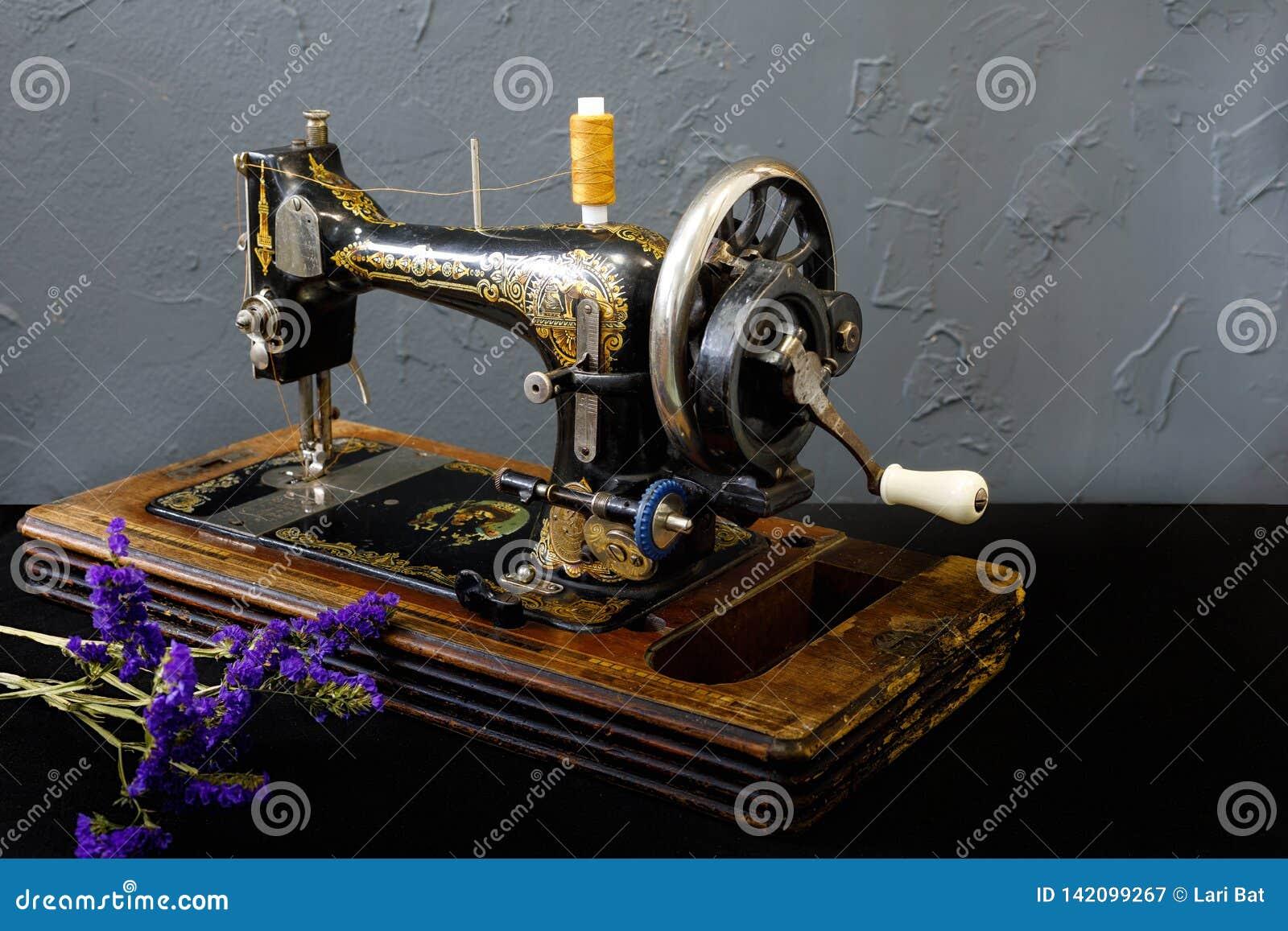 La machine à coudre de cru se tient sur la table blanche