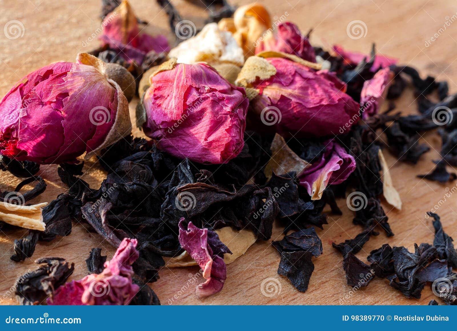 La macro photo du thé avec un thé s est levée La composition du tas des  roses de thé et de la fleur sèche de ketmie situées sur un conseil en bois  Thé ... 92b808ddf18