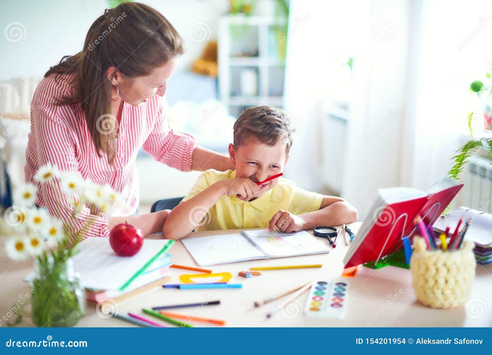 La madre ayuda al hijo a hacer lecciones el enseñar casero, lecciones caseras el profesor particular se involucra con el niño, en