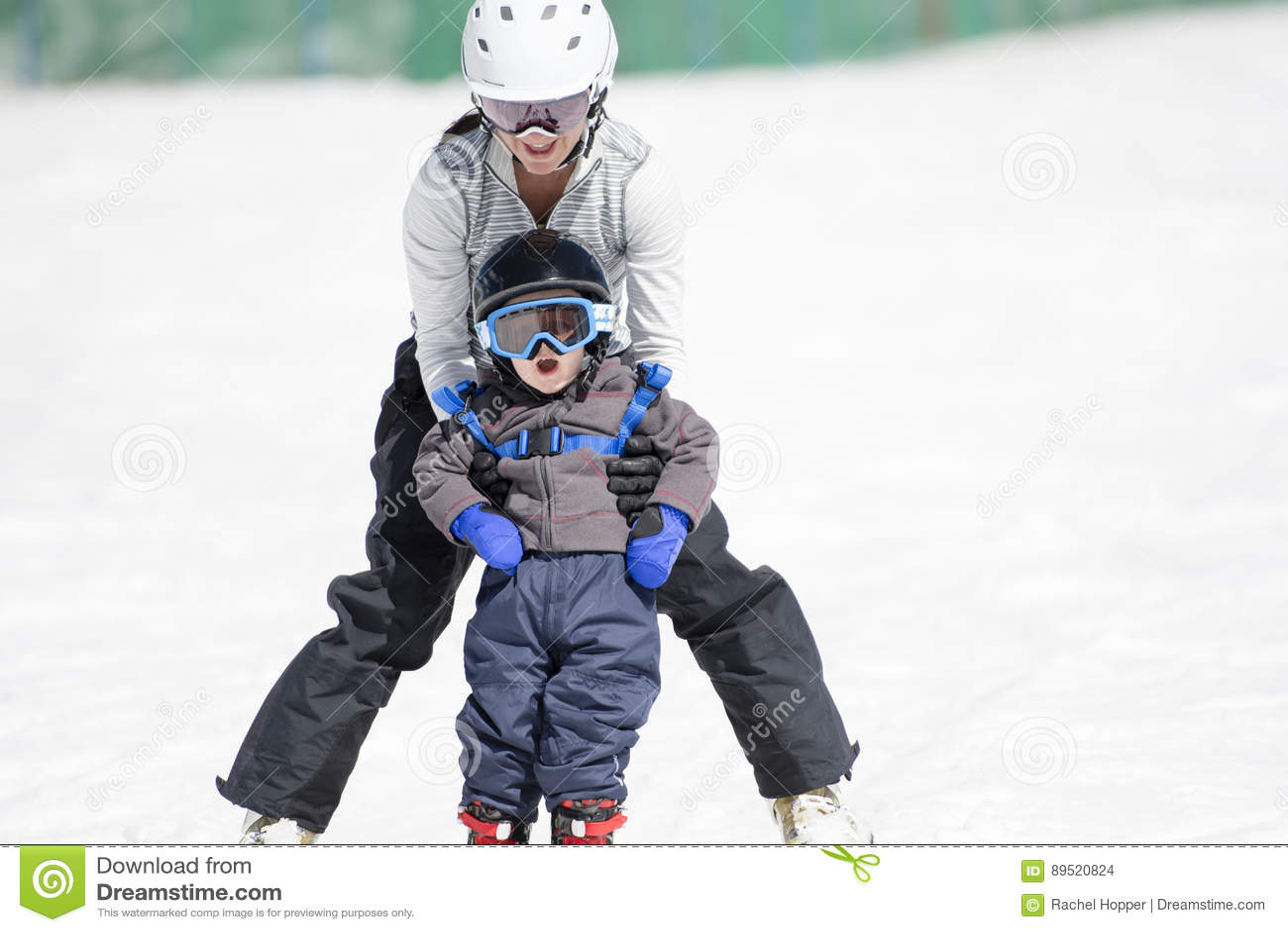 La madre ayuda al muchacho Ski Downhill de Tpoddler Vestido con seguridad