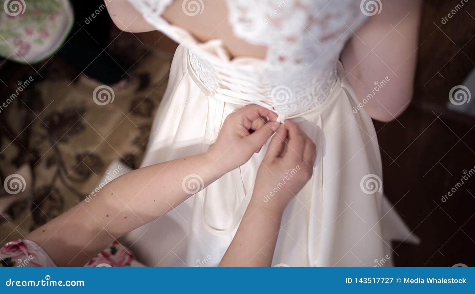 La madre ayuda a la novia a poner un vestido que se casa existencias Las manos atan un corsé de un vestido que se casa