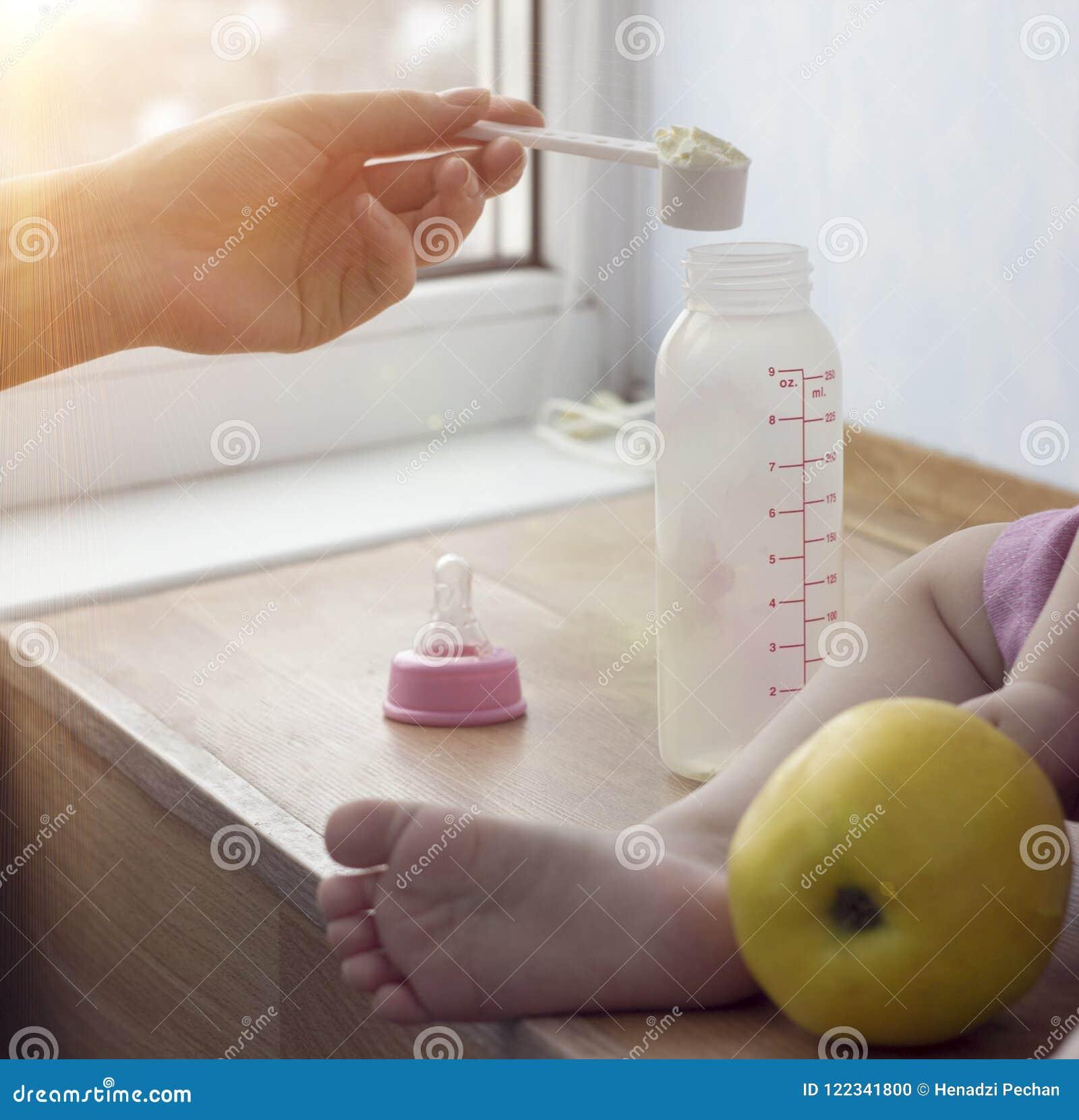 La madre cocina los alimentos para niños para el niño, un cierre para arriba, una mano y una pequeña botella