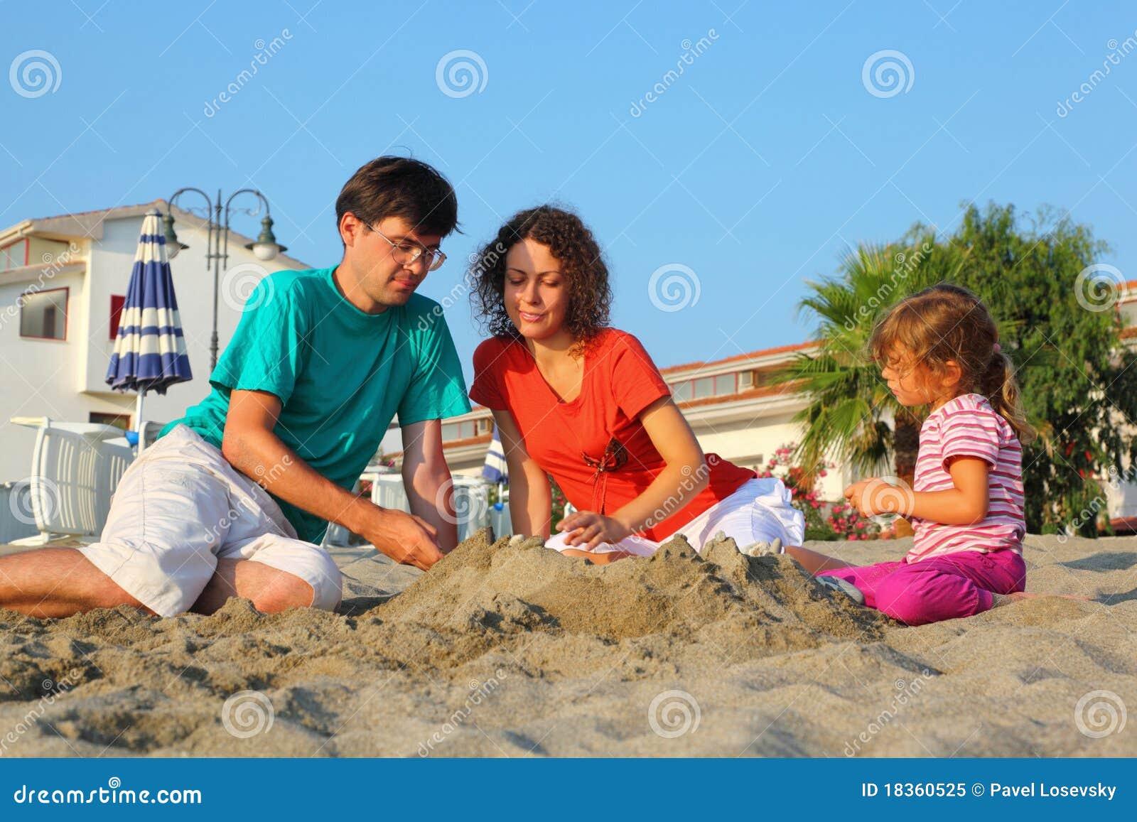 La madre con il padre e la ragazza si siedono sulla spiaggia