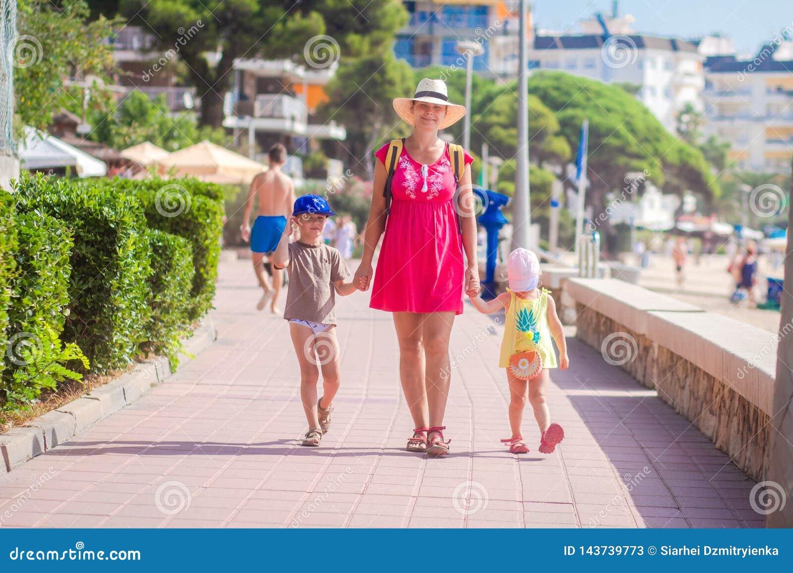 La madre con sus niños va a la playa del mar durante resto tropical