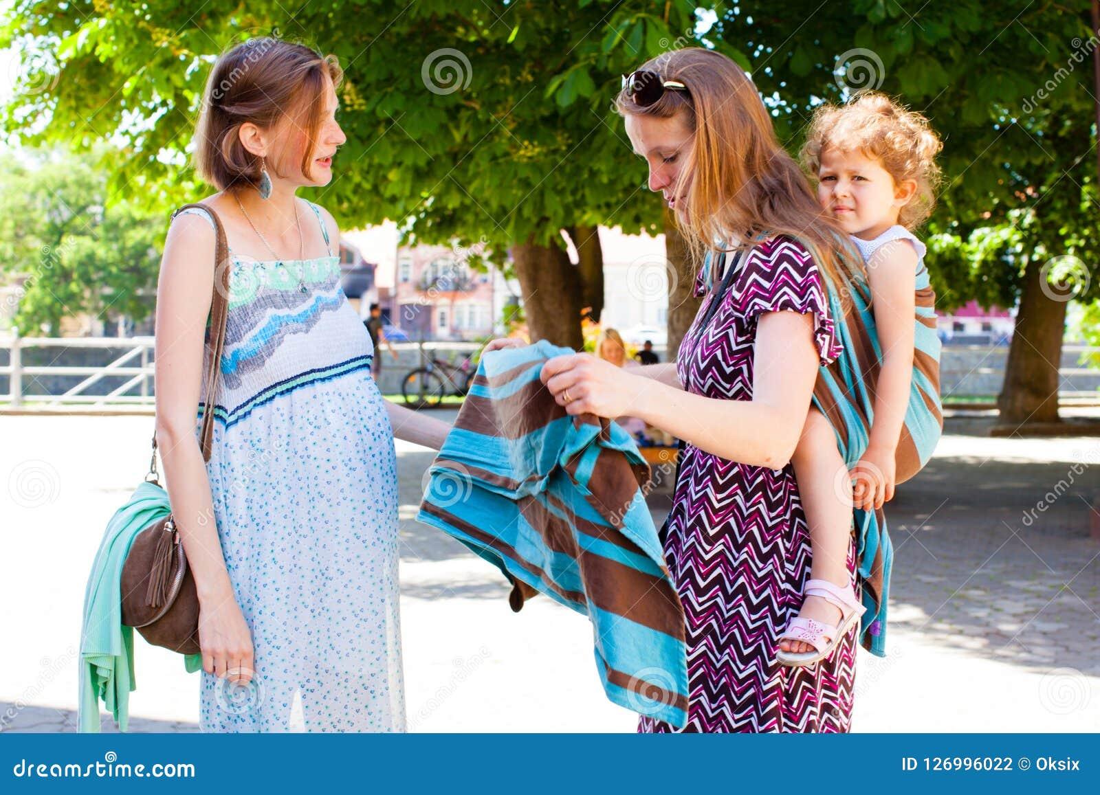 La madre de Babywearing muestra la honda a la señora embarazada