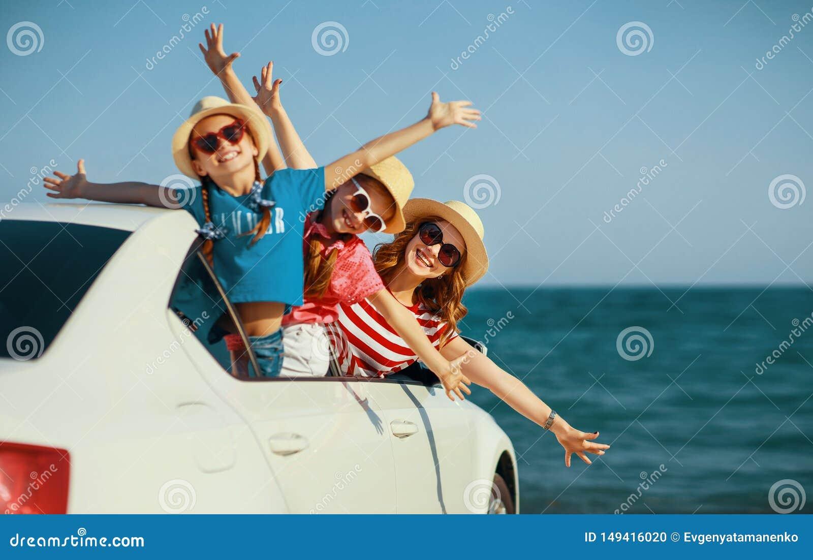 La madre de la familia y las muchachas felices de los ni?os va al viaje del viaje del verano en coche