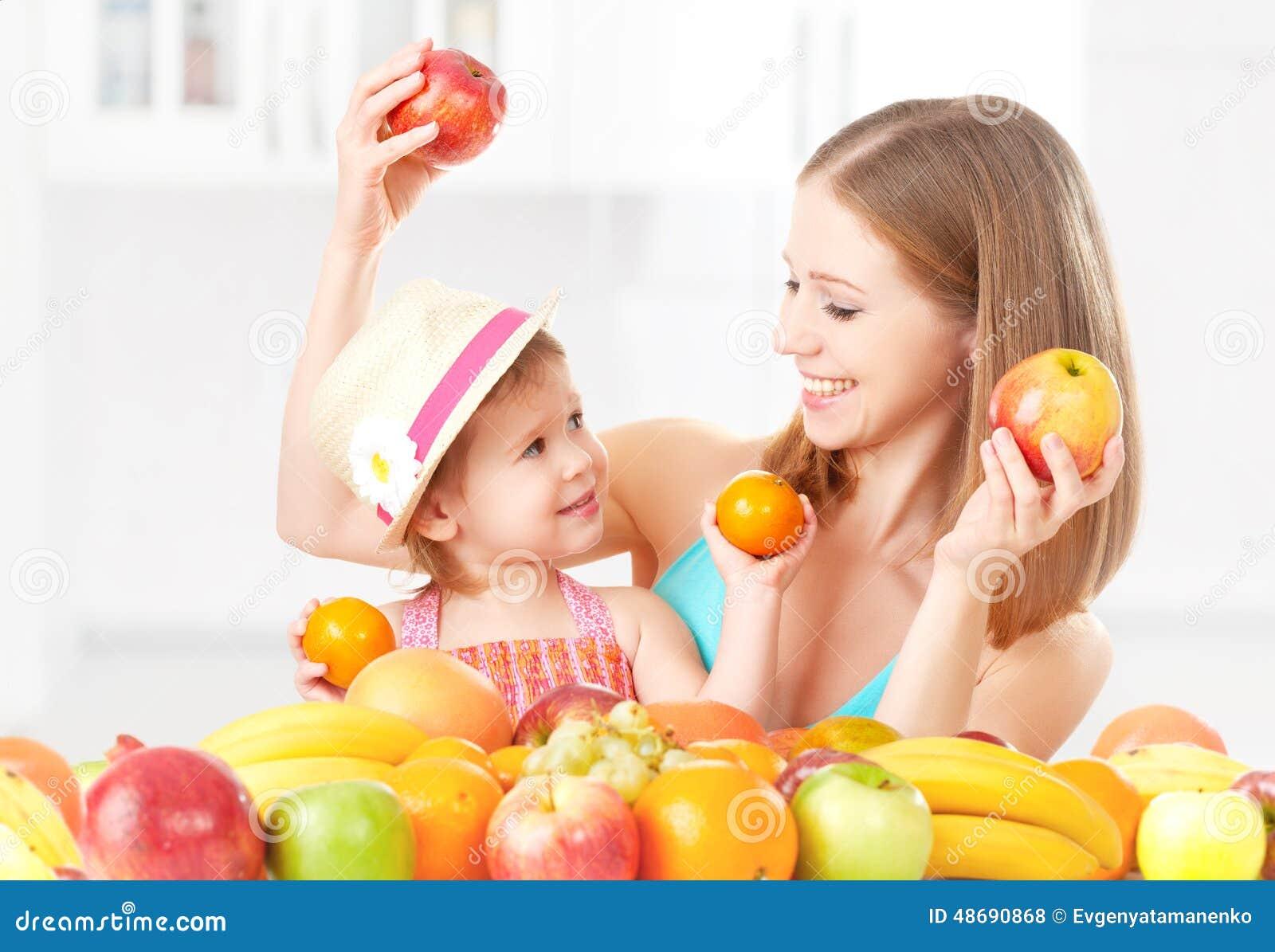 La madre della famiglia e la bambina felici della figlia, mangiano l alimento vegetariano sano, frutta