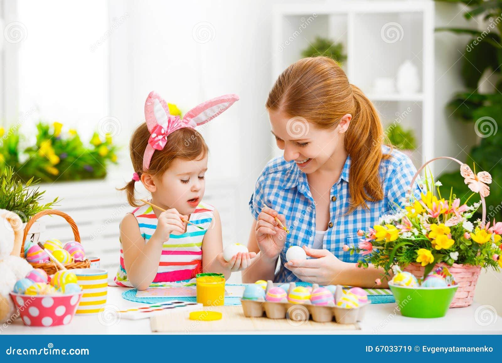 La madre della famiglia e la ragazza felici del bambino dipinge le uova per Pasqua