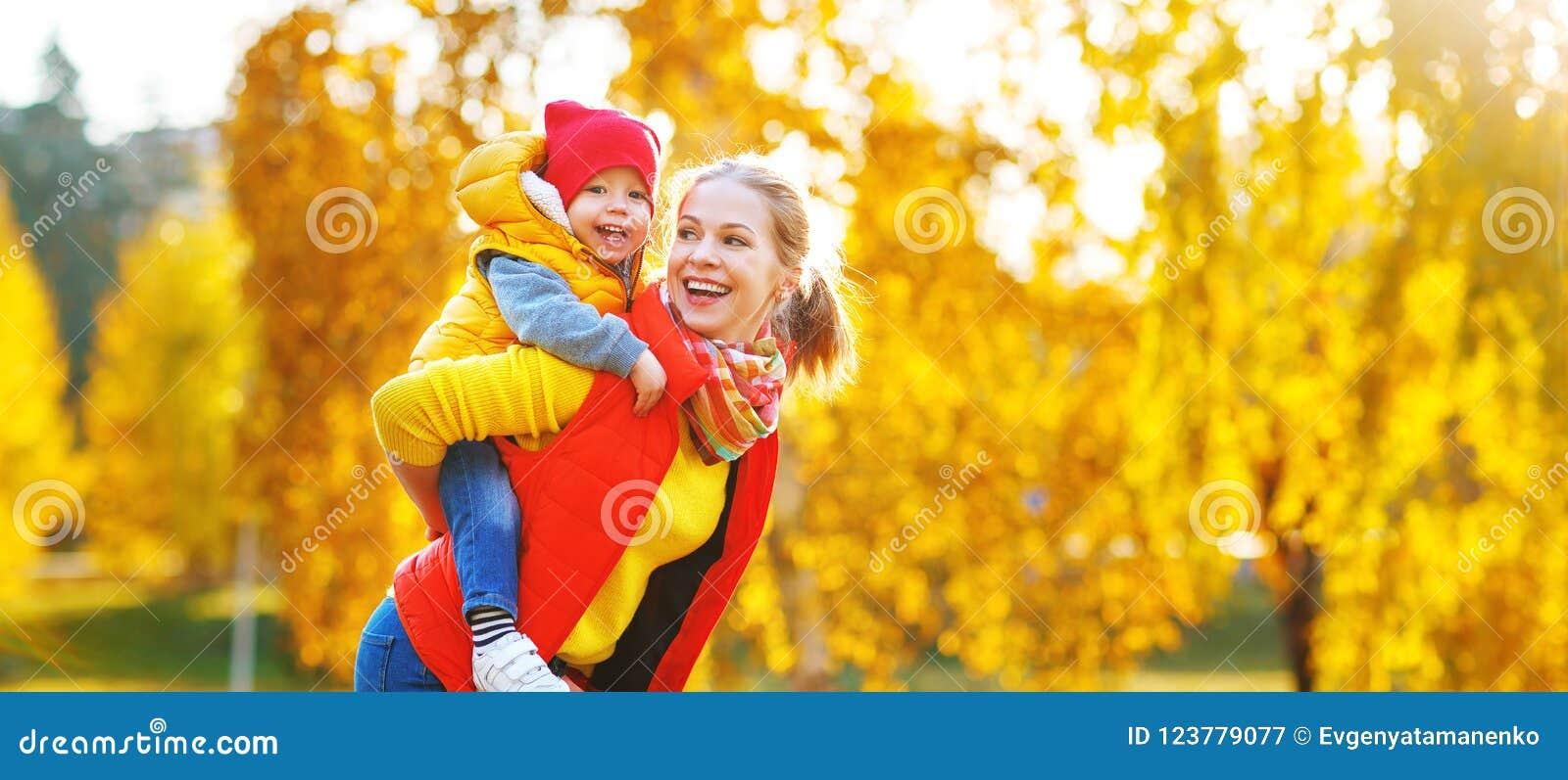 La madre della famiglia ed il figlio felici del bambino sull autunno camminano