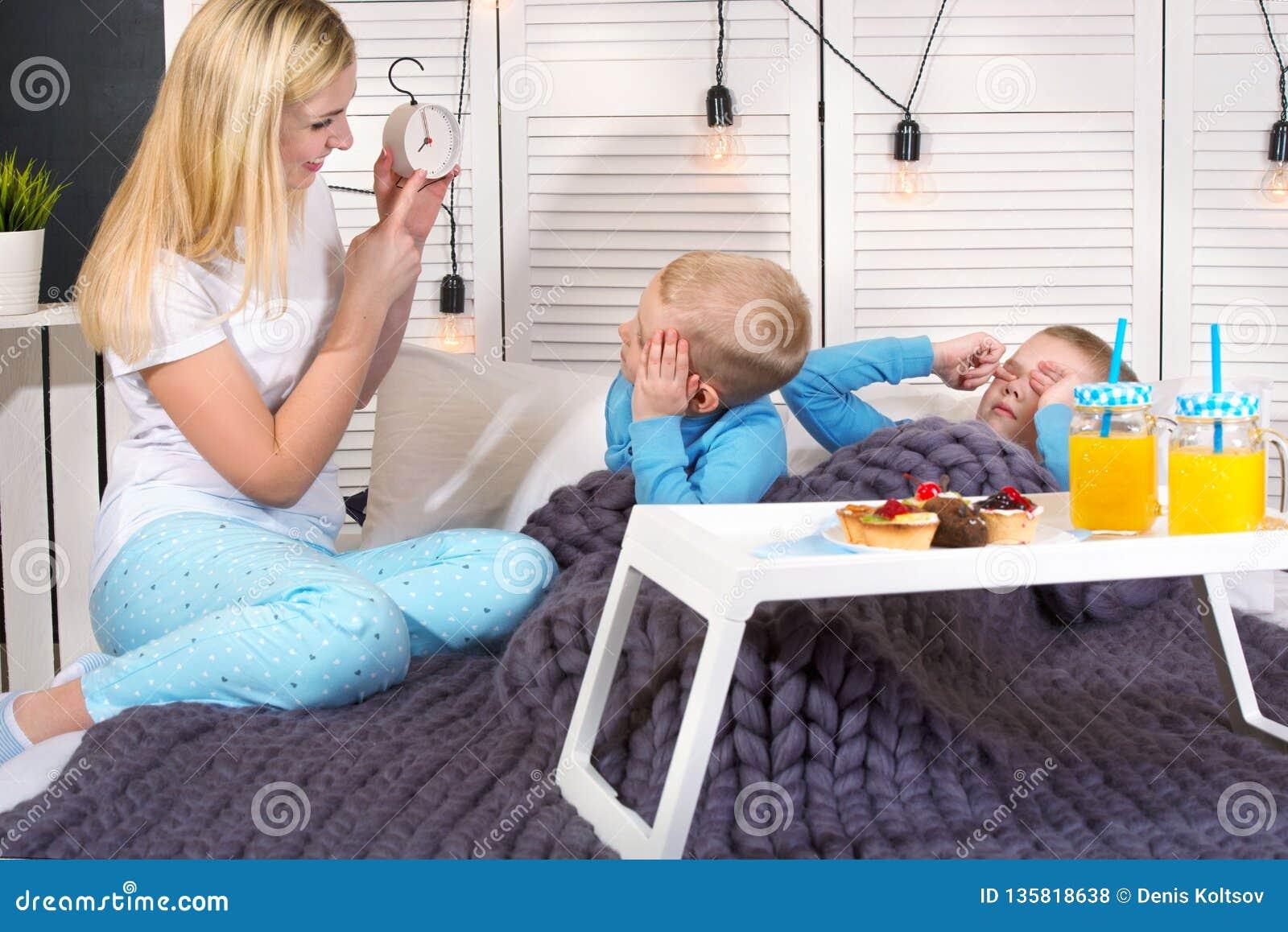 La madre despierta a sus hijos queridos Desayuno en la cama para los niños, sorpresa