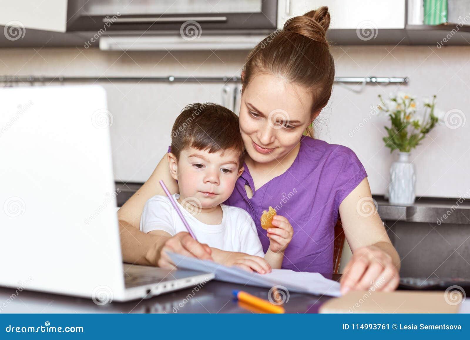 La madre di funzionamento occupato si siede davanti al computer portatile aperto, prova a conecntrate su lavoro, si siede contro