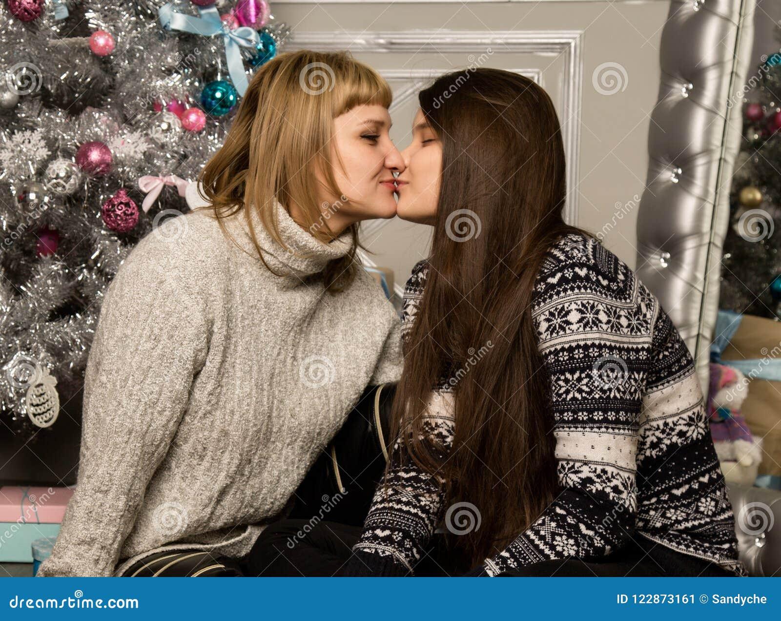 La madre e la figlia felici del teenag vicino all albero di Natale a casa ridono ed abbracciano