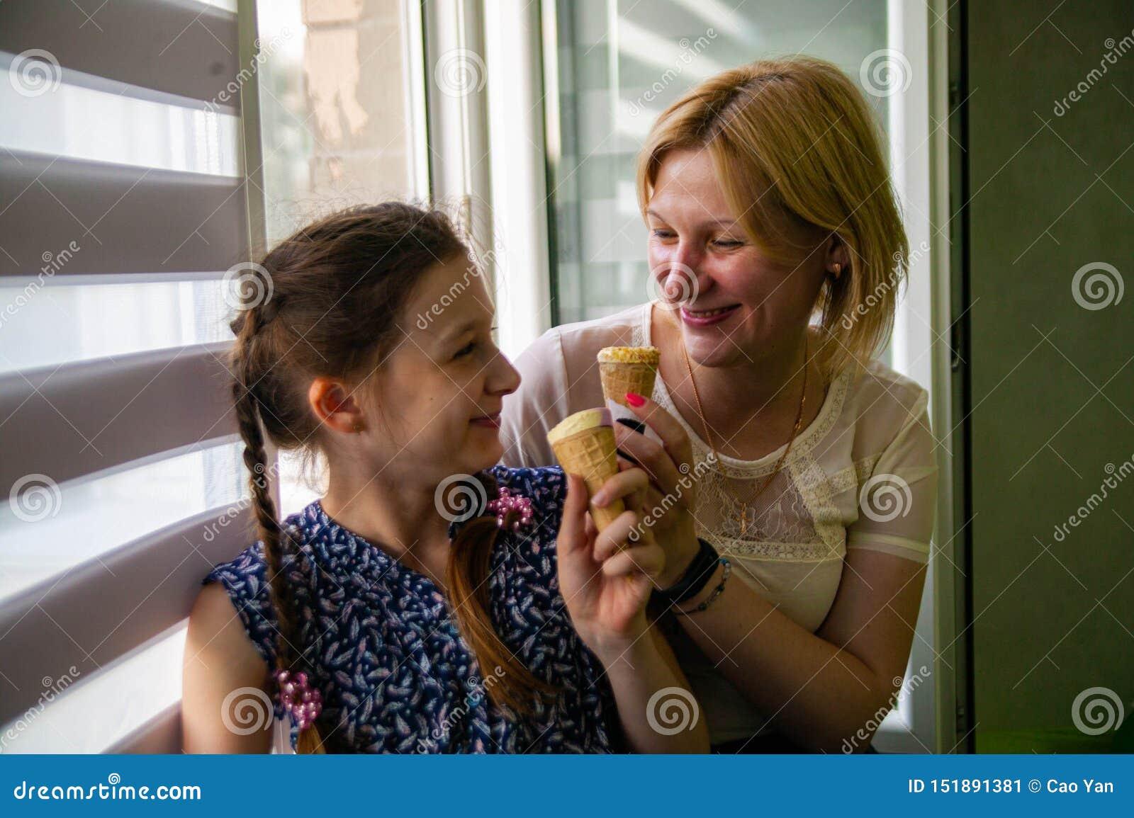 La madre e la figlia sveglia godono del gelato un giorno di estate caldo