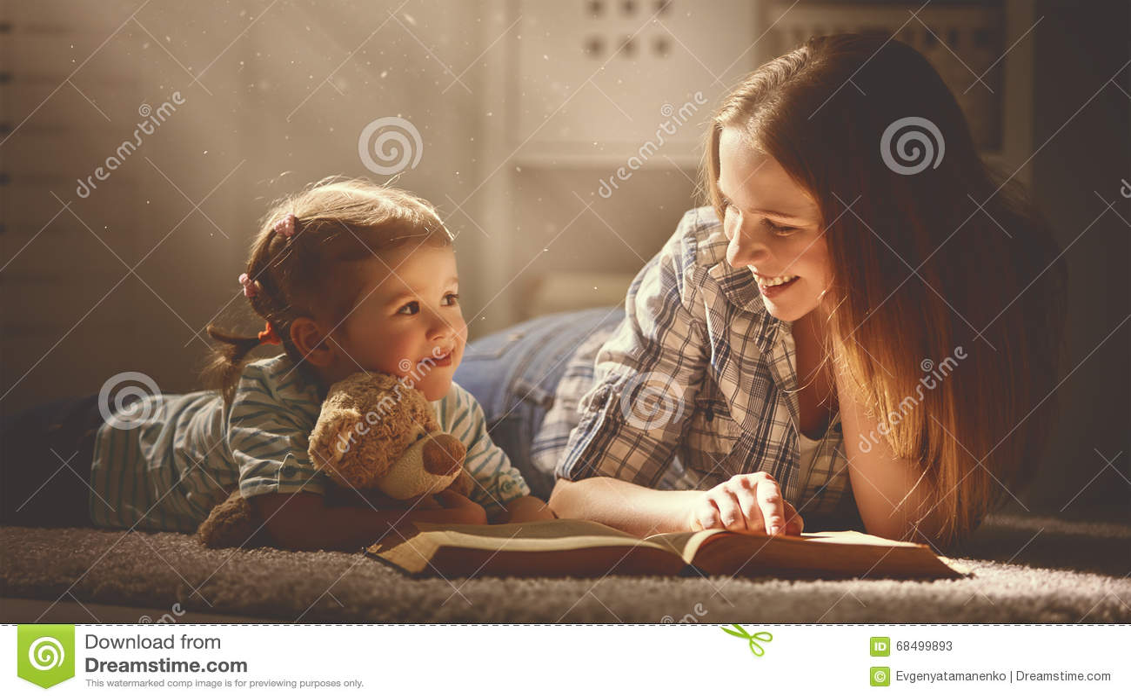 La madre e la figlia felici della famiglia hanno letto un libro nella sera