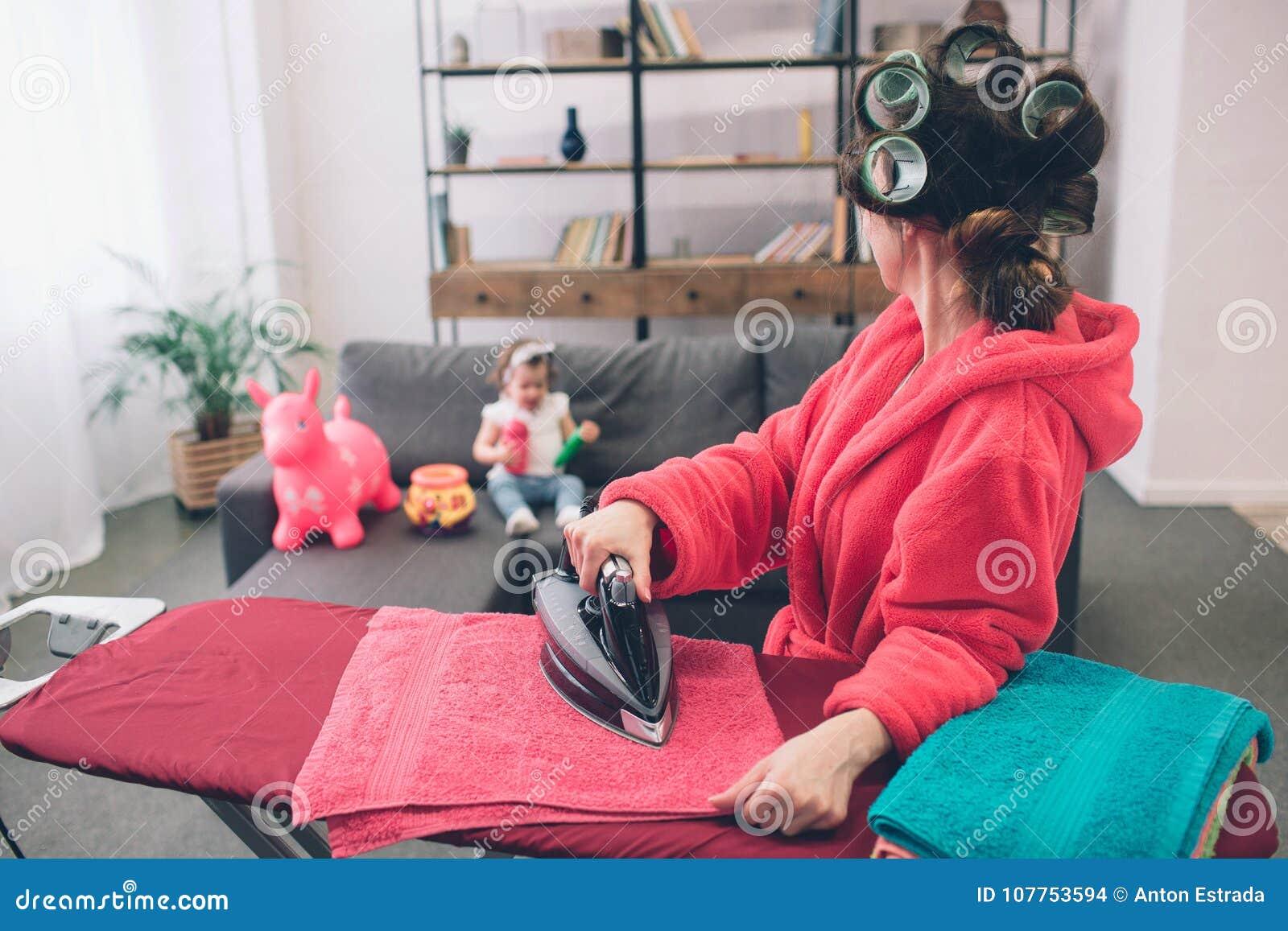 La madre ed il bambino si sono impegnati insieme in vestiti rivestenti di ferro di lavoro domestico Casalinga e bambino che fanno
