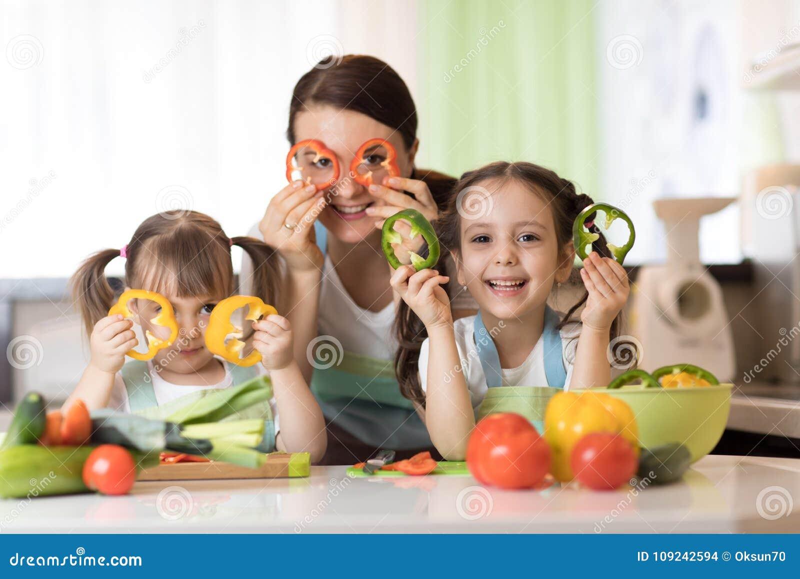 La madre felice ed i bambini della famiglia che si divertono con le verdure dell alimento alla cucina tiene il pepe prima dei lor