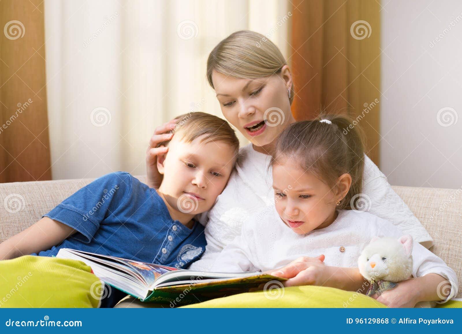 La madre hermosa está leyendo un libro a sus niños jovenes La hermana y el hermano está escuchando una historia