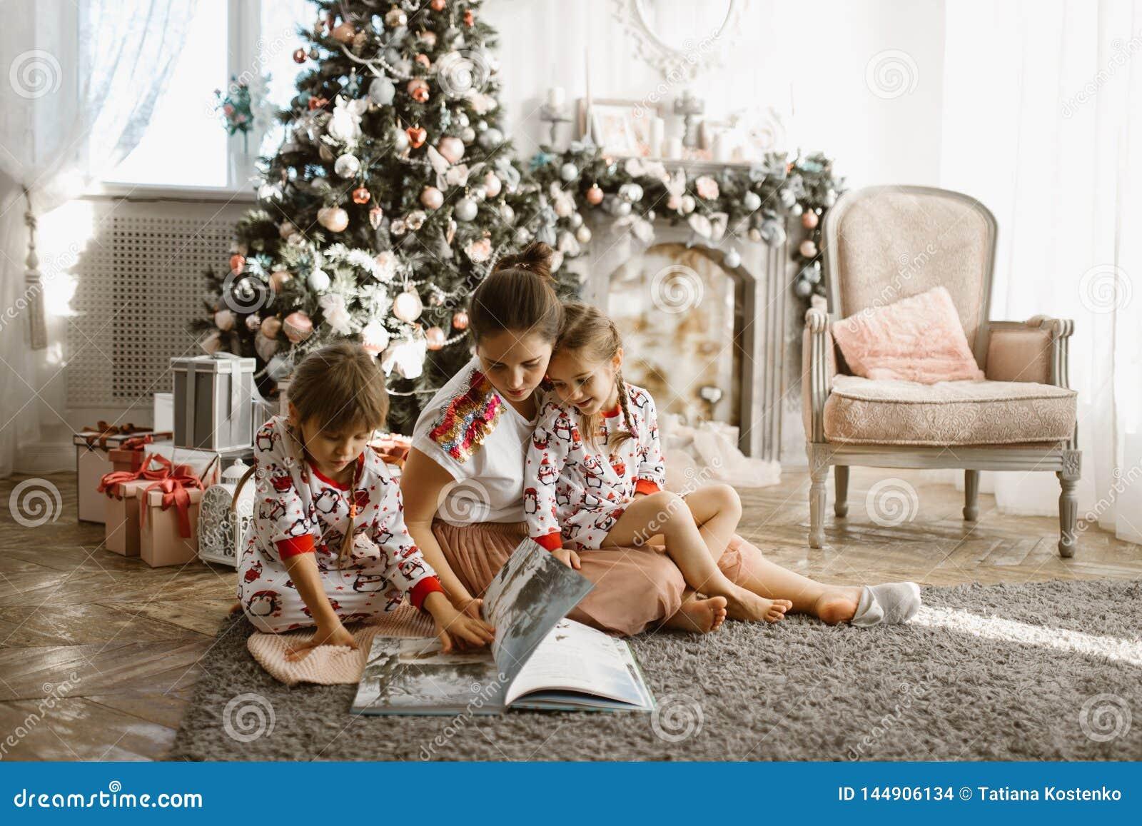 La madre hermosa joven con dos pequeñas hijas se sienta en la alfombra y leyó el libro cerca del árbol del Año Nuevo con los