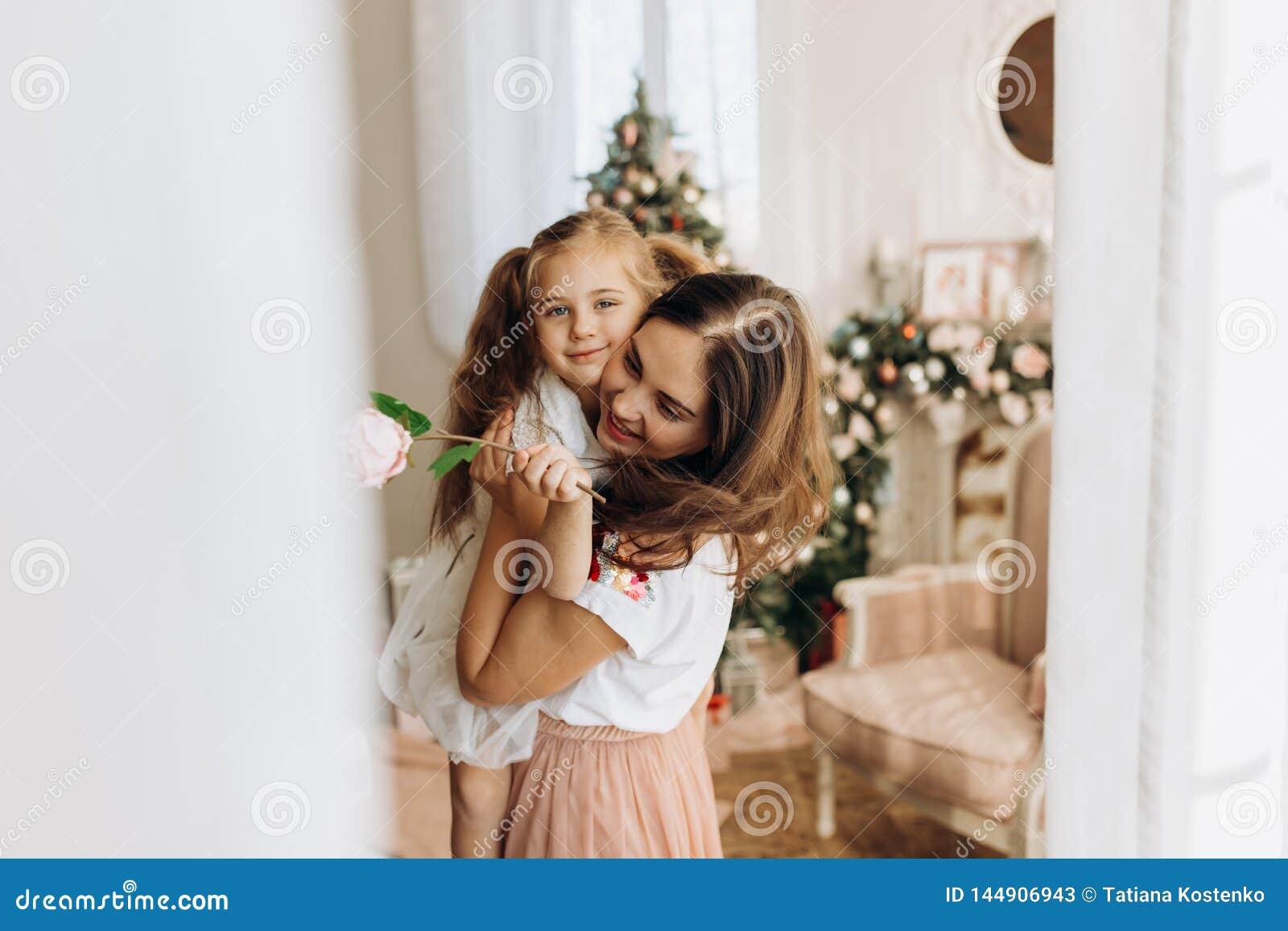 La madre joven celebra en sus manos a su pequeña hija en el cuarto acogedor con el árbol del Año Nuevo
