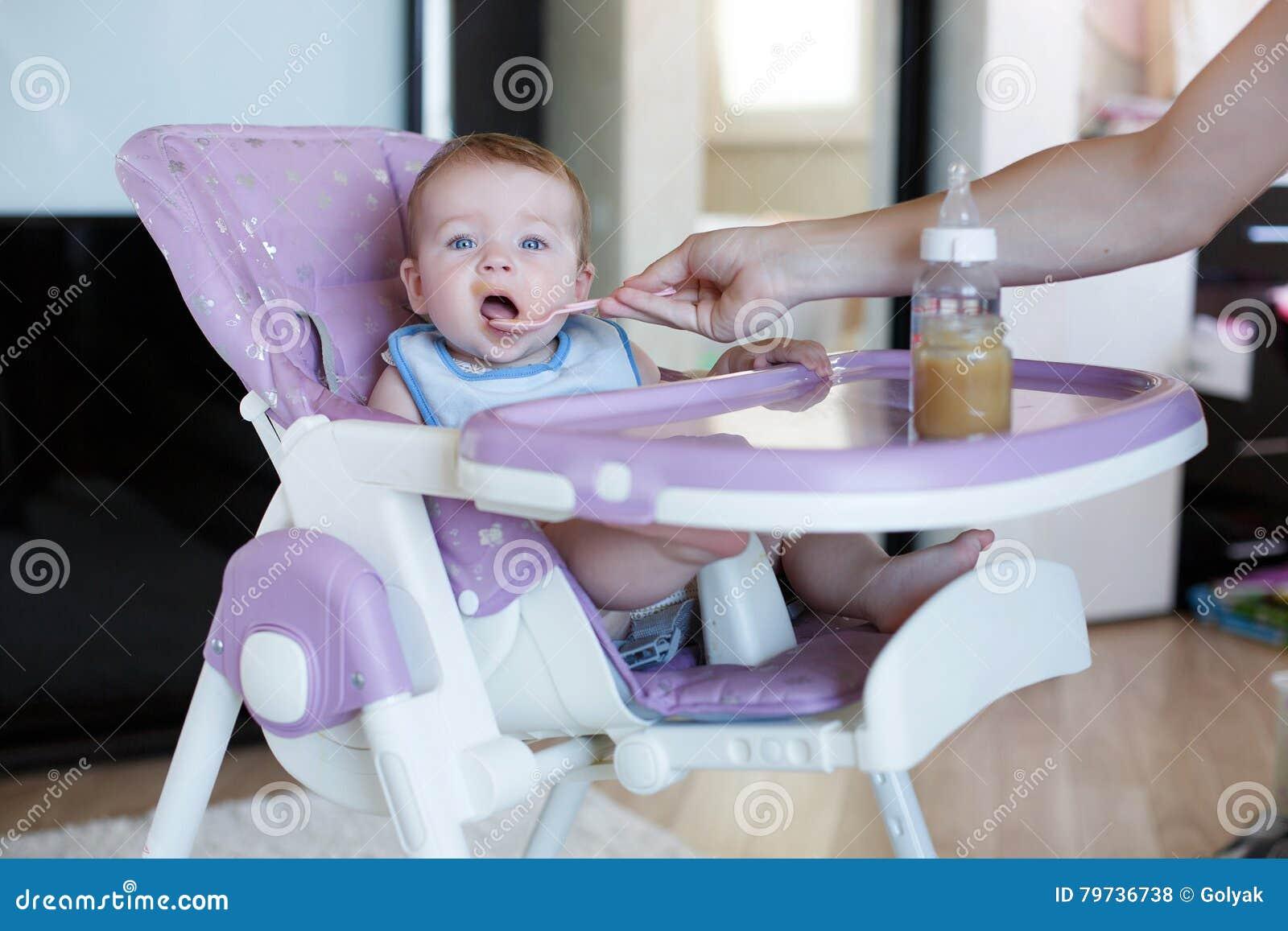 La madre joven da de comer a la boca al niño
