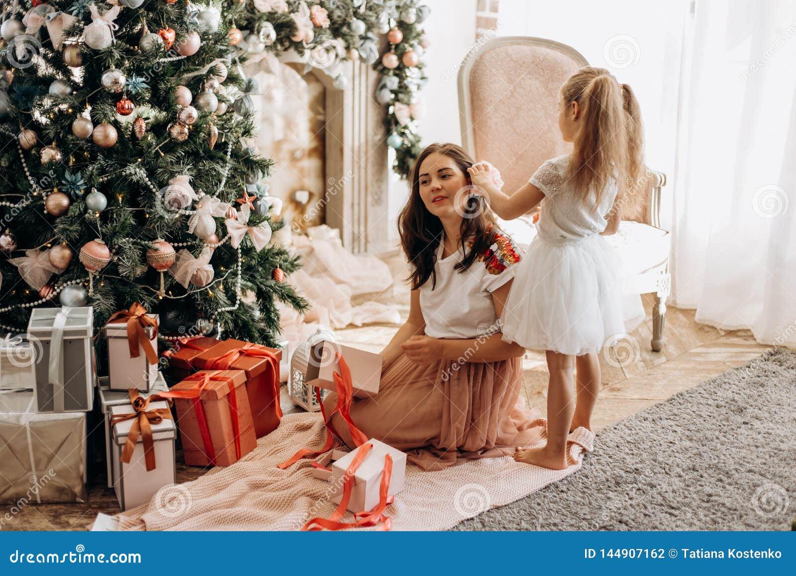 La madre joven feliz y su pequeña hija en vestido agradable se sientan cerca del árbol del Año Nuevo y de los regalos abiertos
