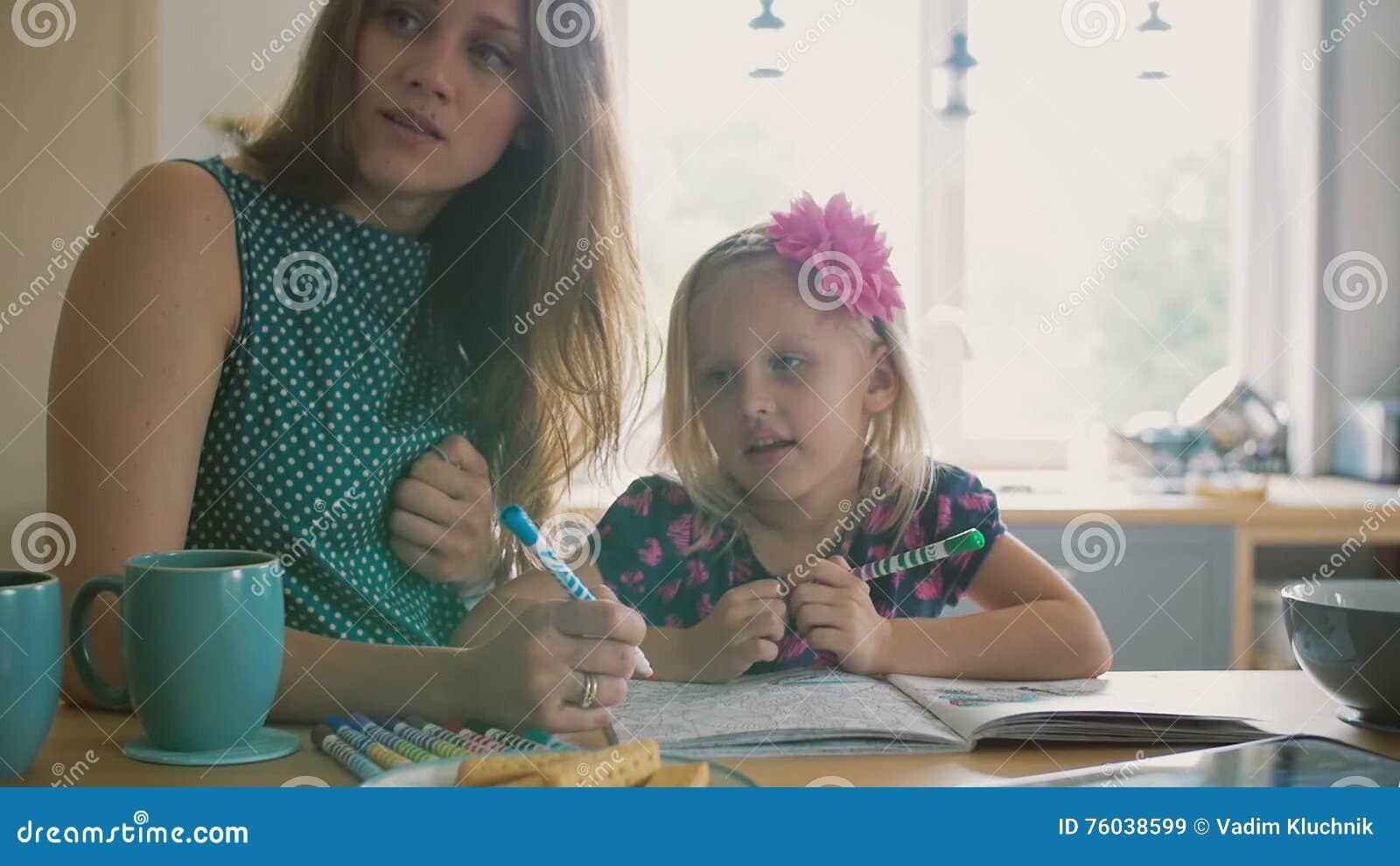 La Madre Joven Hermosa Está Ayudando A Su Pequeña Hija Rubia A ...