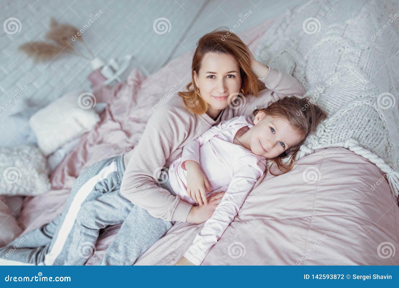 La madre joven hermosa y su pequeña hija están mintiendo juntas en la cama en el dormitorio, están jugando, están abrazando y se