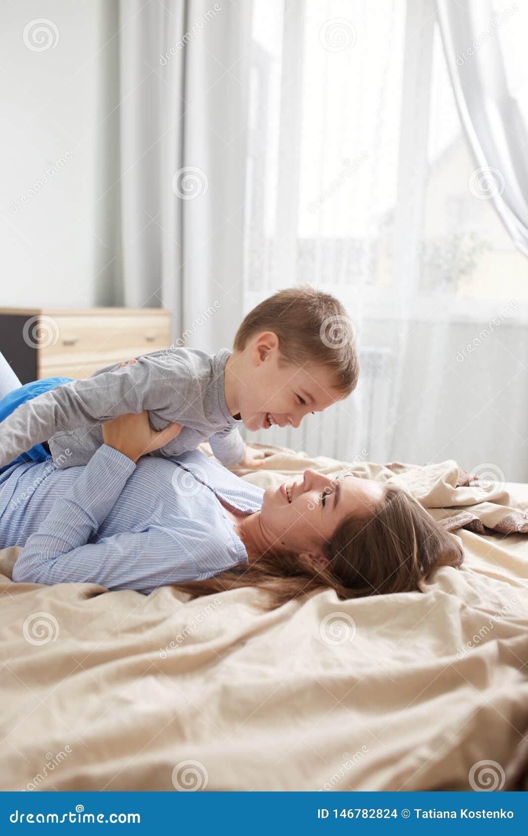 La madre joven vestida en pijama azul claro pone en la cama con la manta beige y detener a su peque?o hijo en sus manos en