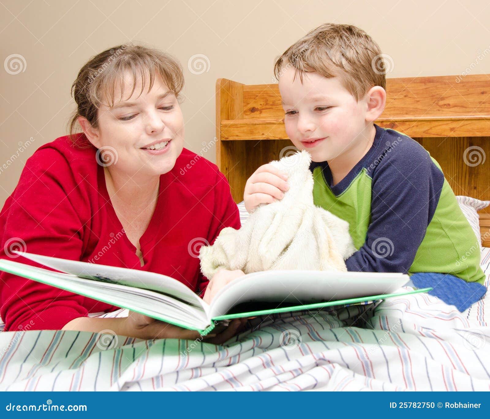 La madre legge la storia di ora di andare a letto al giovane ragazzo
