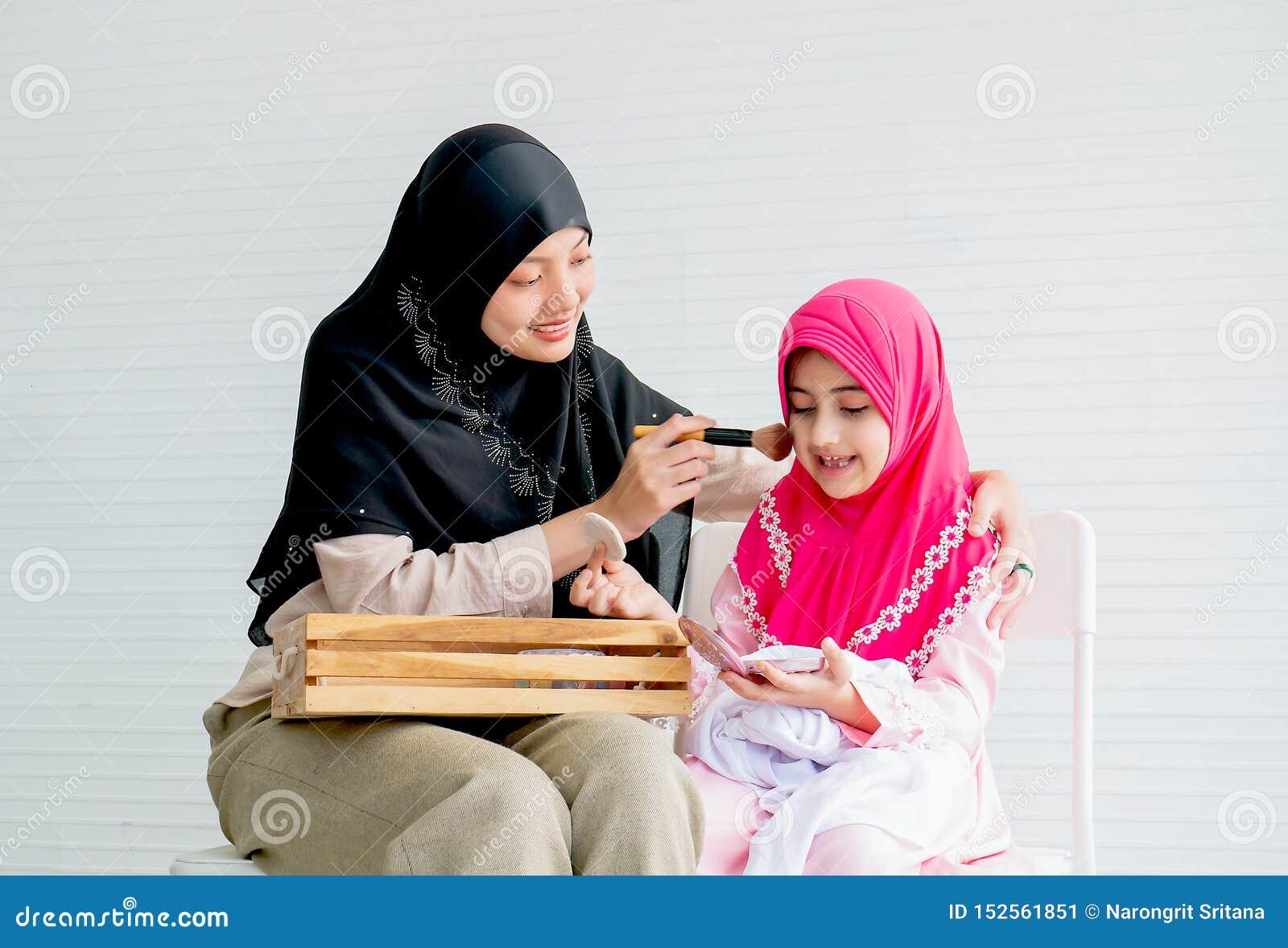 La madre musulmán y su hija son imponen con actividad cosmética juntas en el cuarto con el espacio blanco del fondo y de la copia