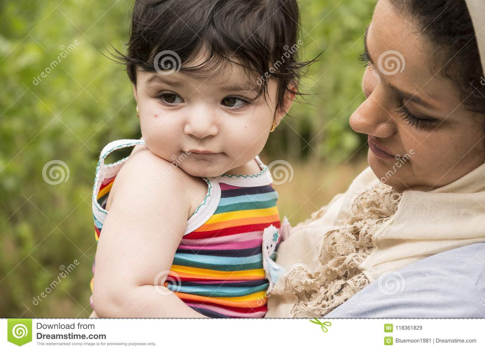 La madre musulmana ha abbracciato un piccolo bambino in enjo all aperto di area della natura