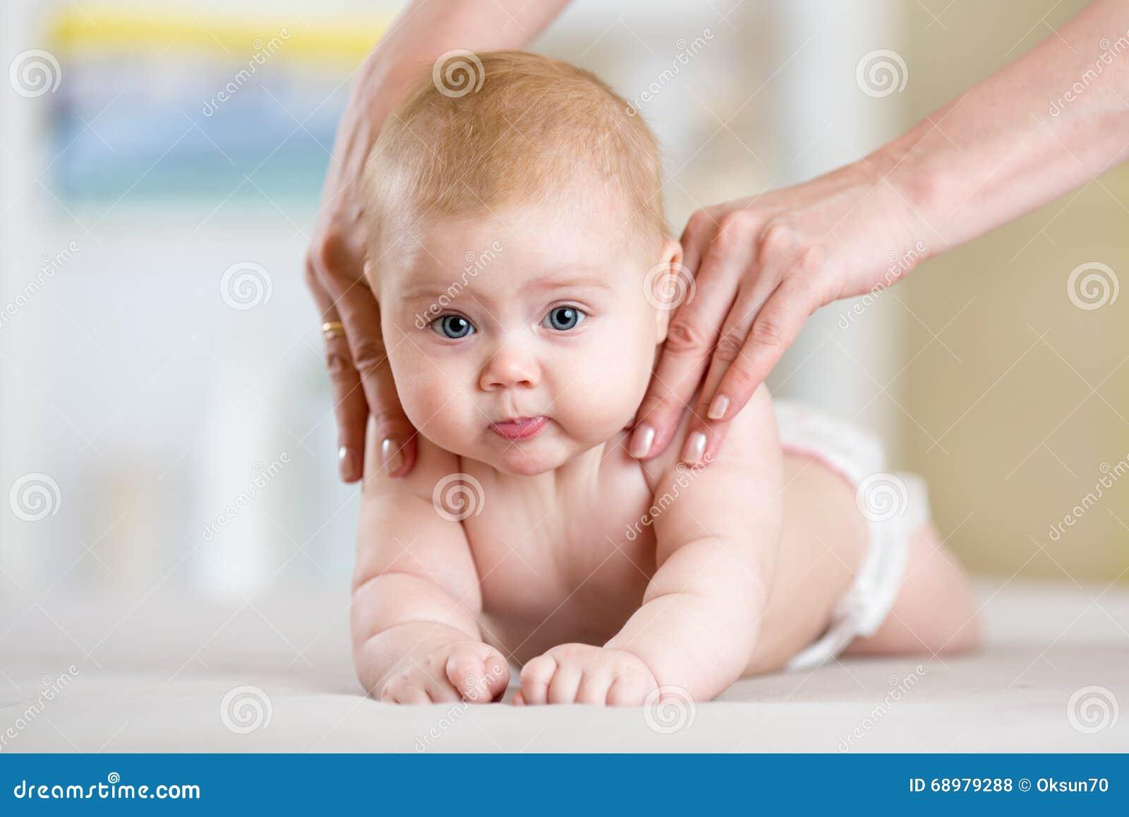 La madre o el terapeuta hace masaje a su bebé en casa Concepto de la atención sanitaria y de la medicina