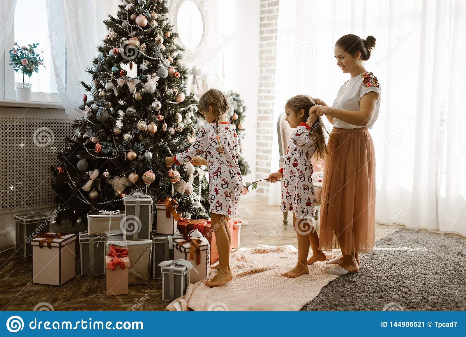La madre preoccupantesi intreccia la treccia della sua piccola figlia mentre la figlia di secondo decora l albero di un nuovo ann