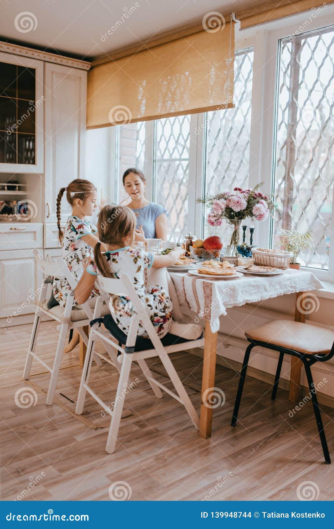 La madre que cuida joven y sus dos pequeñas hijas desayunan en la cocina ligera con la ventana grande
