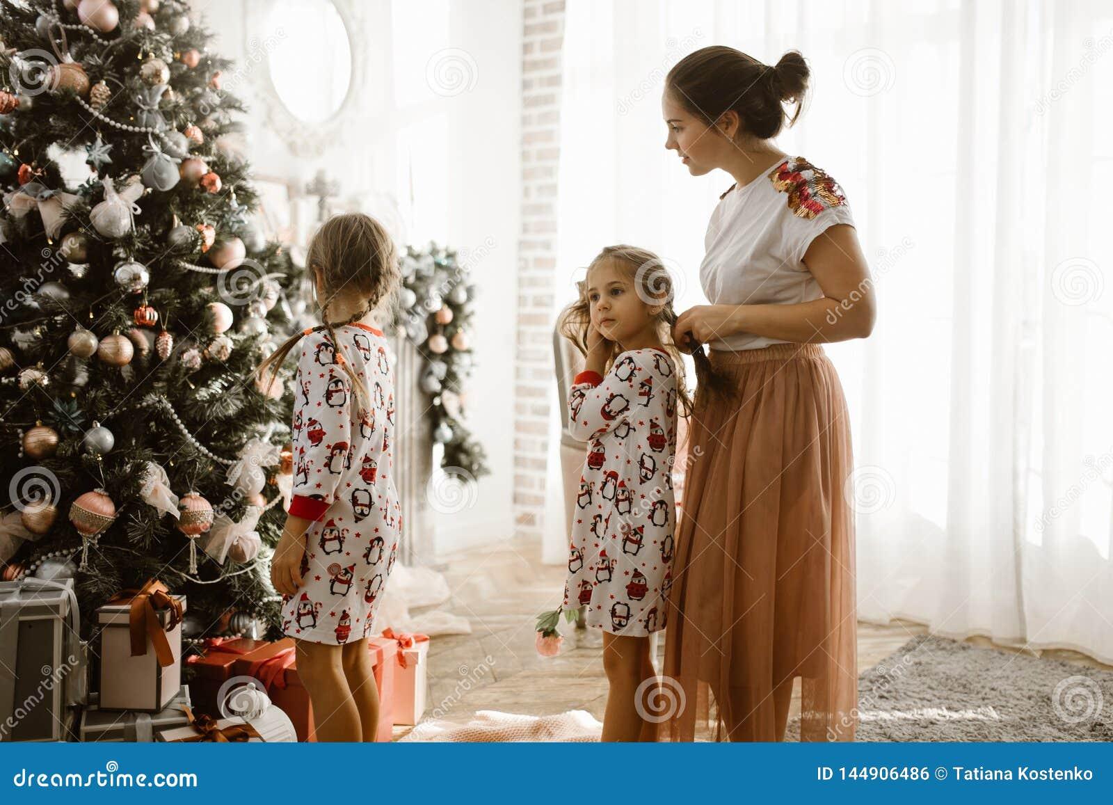 La madre que cuida trenza la trenza de su pequeña hija mientras que la hija del segundo adorna un árbol del Año Nuevo en la lu