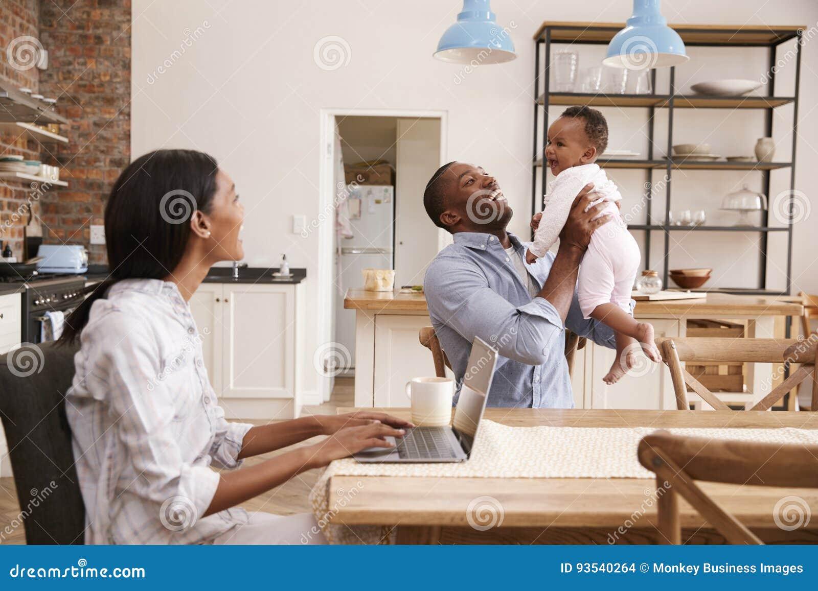 La madre trabaja de hogar como padre Holds Baby Daughter