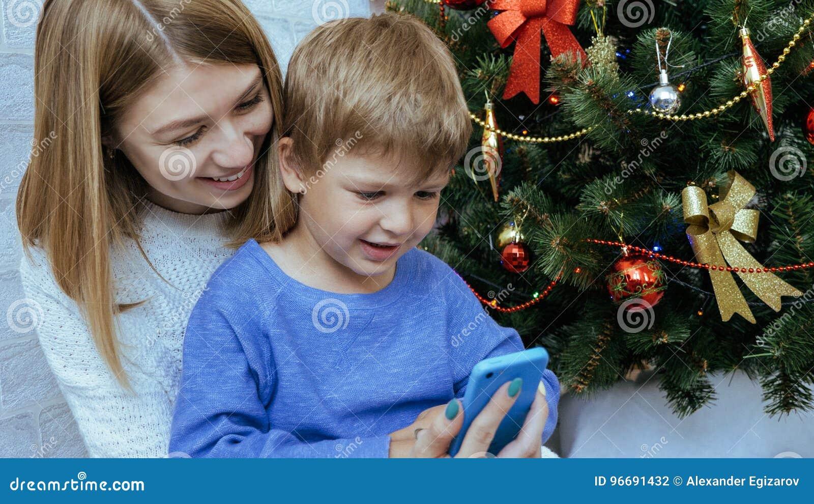 La madre y el hijo con el teléfono móvil se están sentando juntos cerca del árbol de navidad
