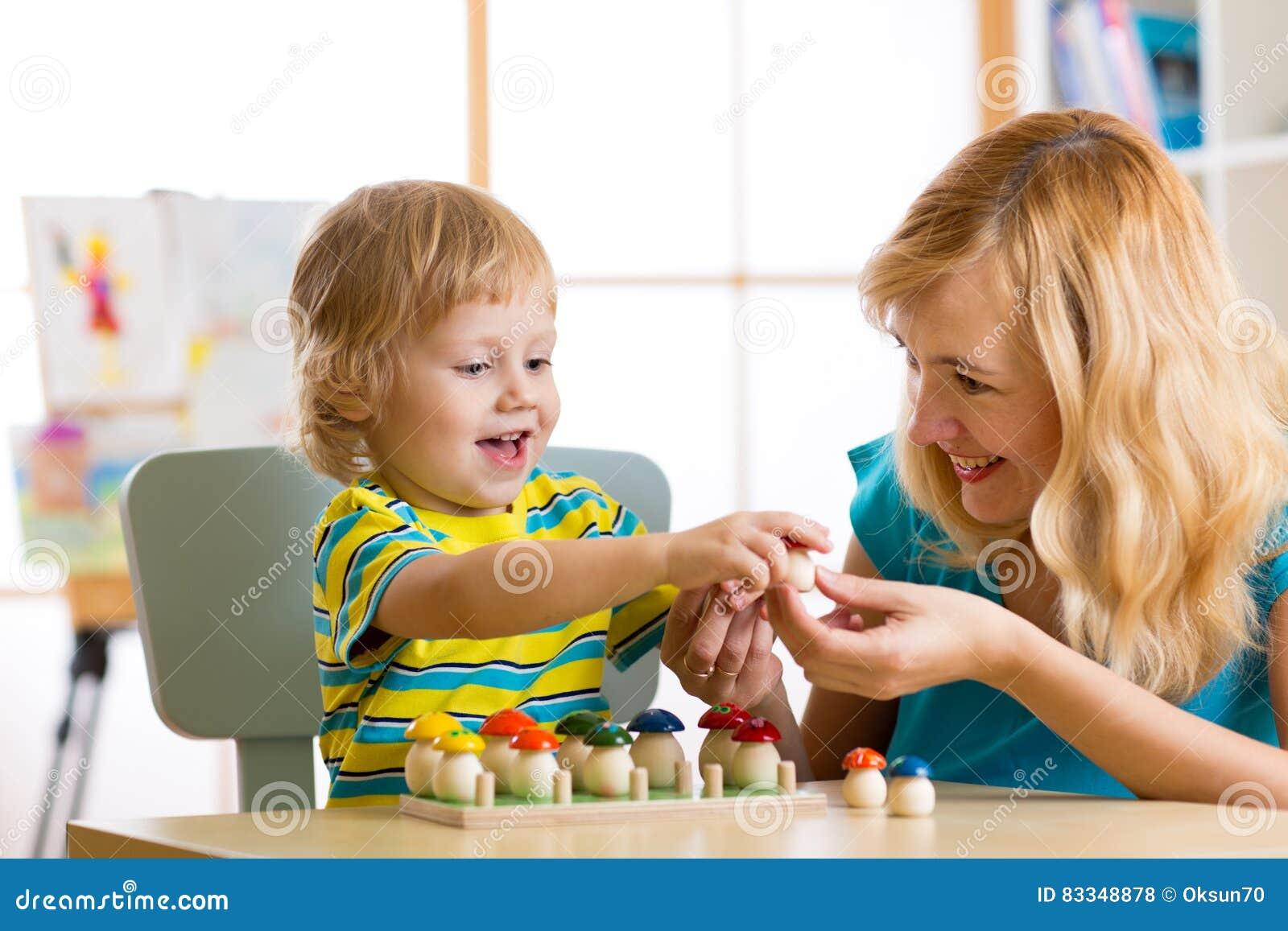 La madre y el niño aprenden color, clasifican, cuentan mientras que juega con los juguetes de desarrollo Concepto temprano de la