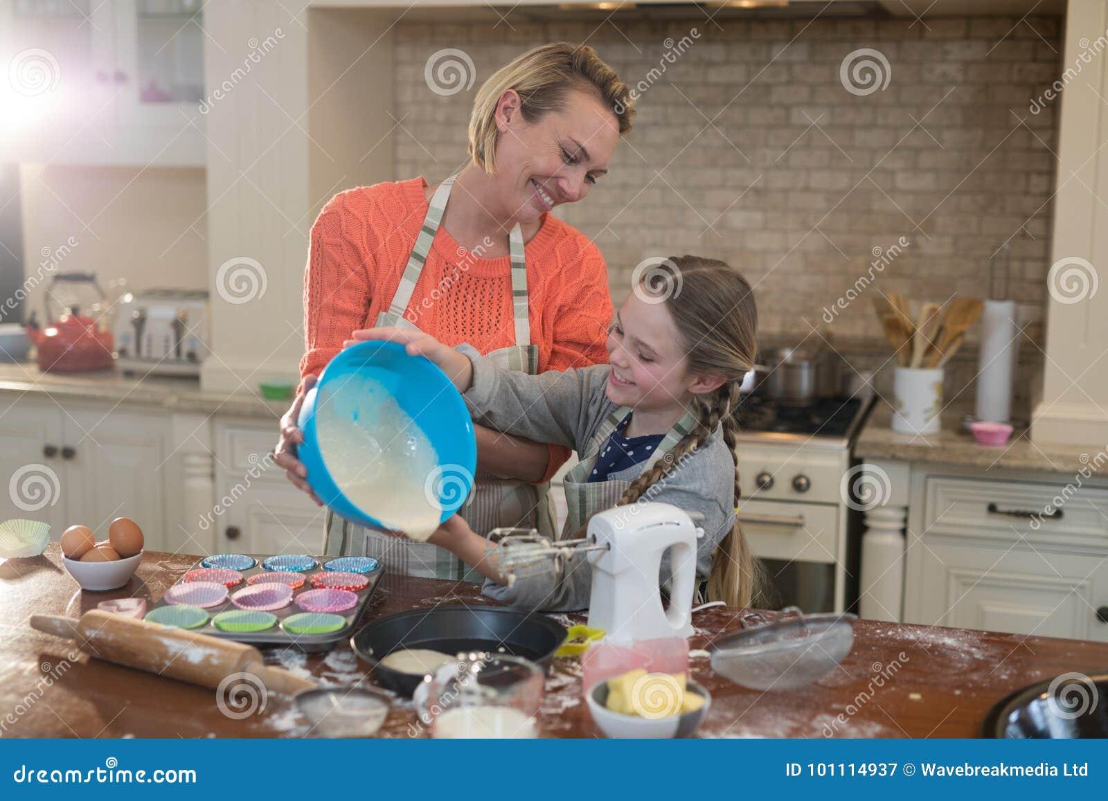 La madre y la hija que preparan la taza se apelmazan en cocina