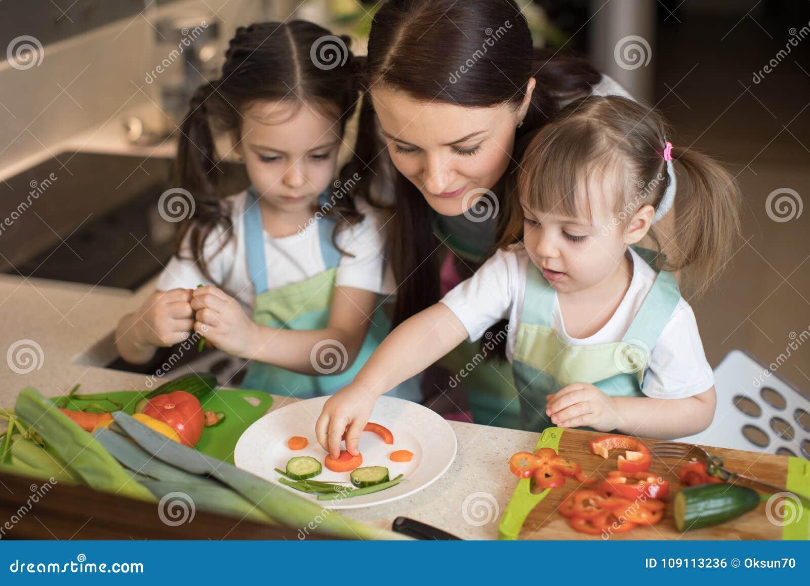 La madre y los niños felices de la familia están preparando la comida sana, ellos hacen la cara divertida con el bocado de las ve