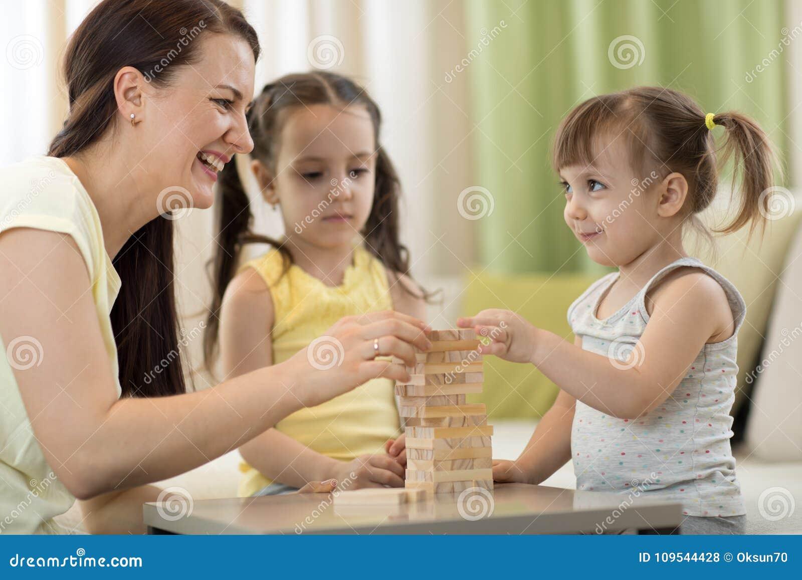 La madre y sus pequeñas hijas están jugando con el juego de mesa