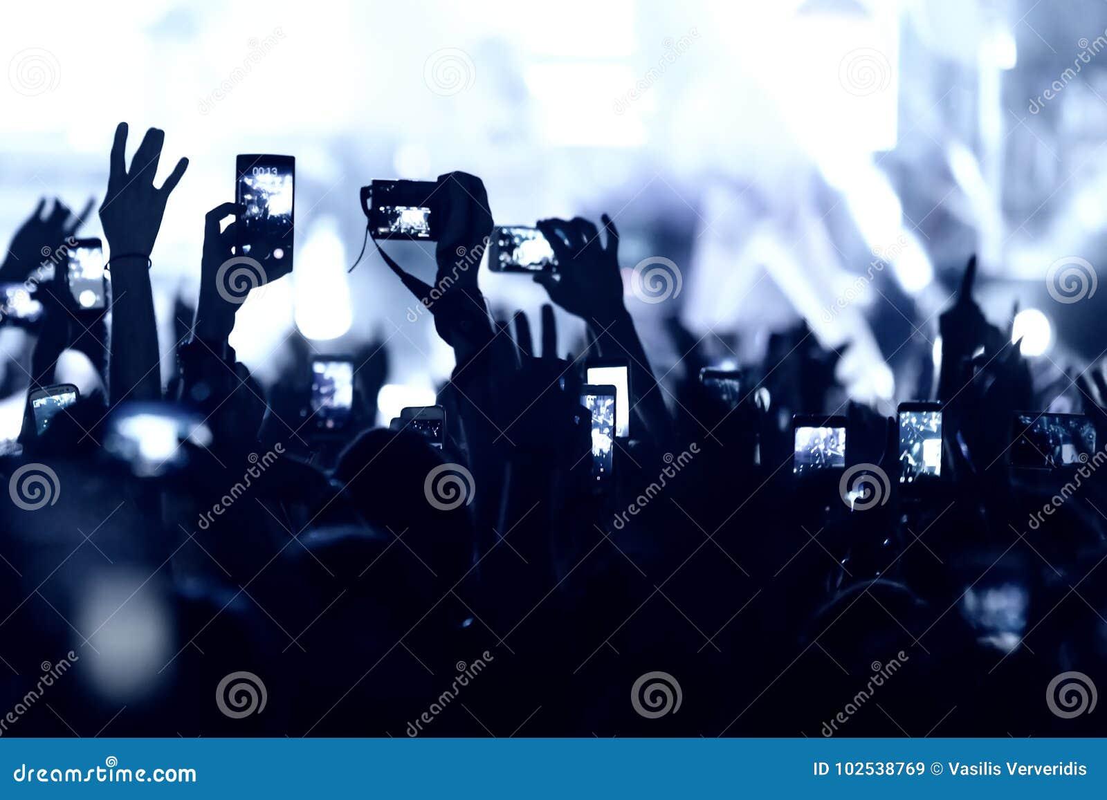 La main avec un smartphone enregistre le festival de musique en direct